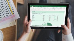 Un homme tenant en main un ordinateur dont l'écran présente un tableau Excel