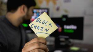 """Une personne tenant une enveloppe sur laquelle est écrit """"Blockchain""""."""